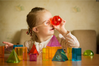 Little girl playing with toys of different shapes